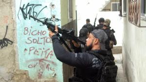 Policial apontando a arma para cima durante operação da favela do Jacarezinho, no Rio de Janeiro