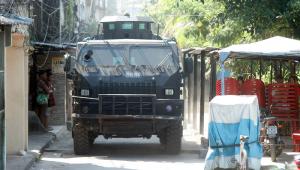 Carro blindado da polícia passa por rua estreita na favela do Jacarezinho e é observado por alguns poucos moradores