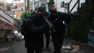 Imagem de quatro policiais na rua com armas na mão