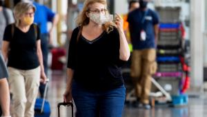 Passageira ajusta a sua máscara ao chegar no Aeroporto de Washington