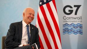 Presidente Joe Biden rindo. Ao fundo, a bandeira dos Estados Unidos e símbolo do G7