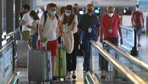 Turistas com máscaras e malas subindo na escada rolante de aeroporto Adolfo Suárez, na Espanha