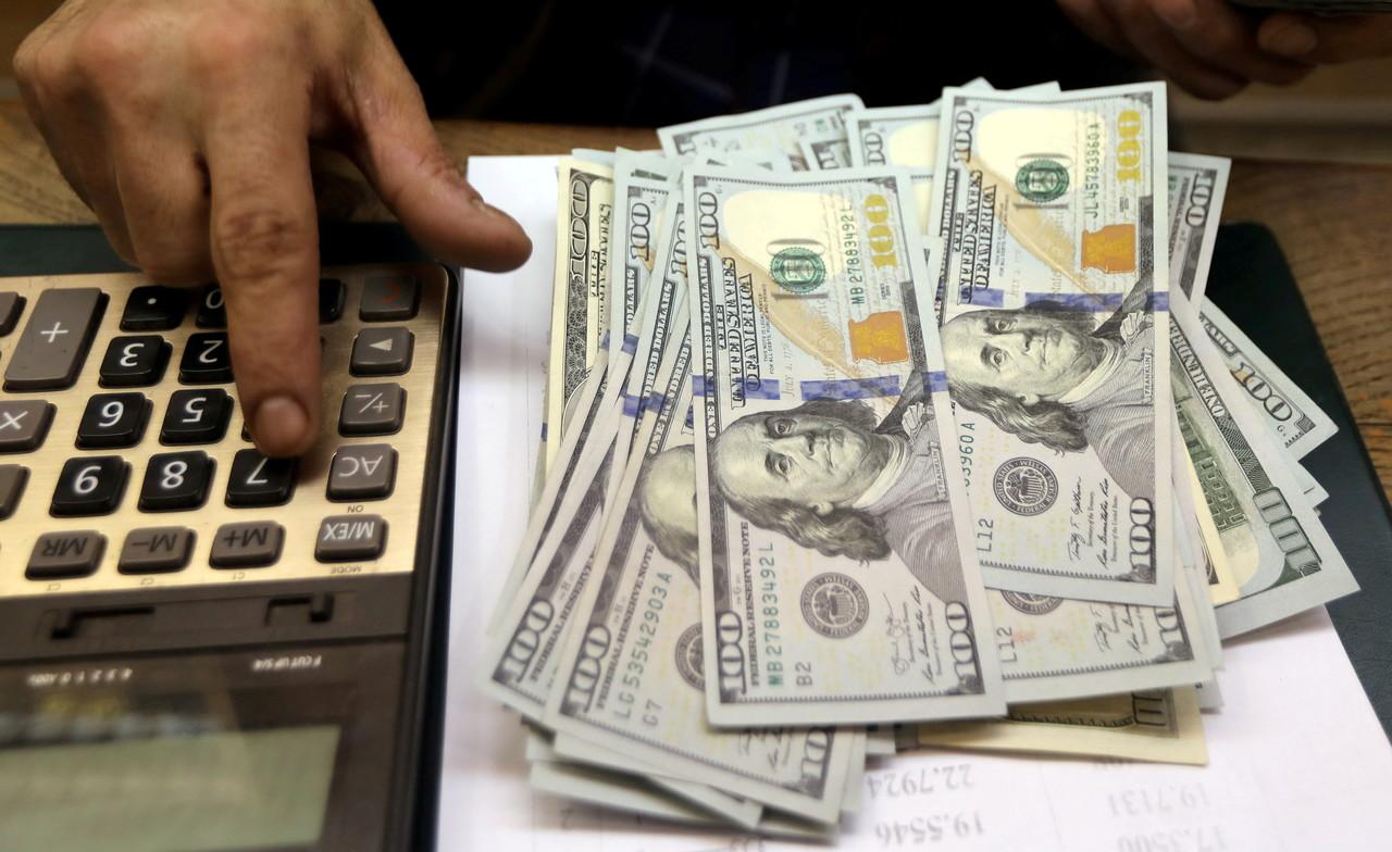 Homem mexe em calculadora; ao seu lado há uma pilha de dólares