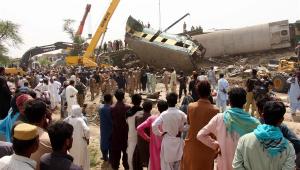 Pessoas na frente dos destroços da colisão entre dois trens no Paquistão