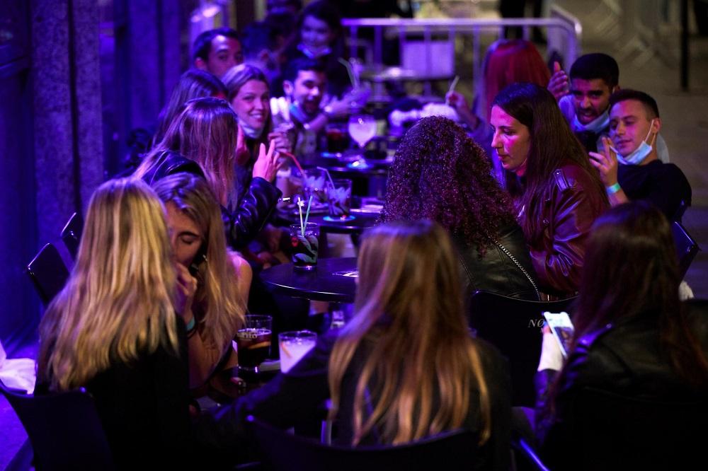 Dezenas de jovens namoram e conversam em um bar com mesas na calçada