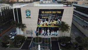 Sede da Confederação Brasileira de Futebol (CBF) na Barra da Tijuca. Prédio com um banner escrito '50 anos do Tri' com jogadores comemorando. O prédio é de cor clara e tem algumas árvores na frente e o símbolo da CBF