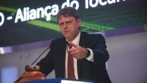 De terno preto, camisa branca e gravata vermelha, o ministro Tarcísio de Freitas fala de cima de um palco onde se vê um martelo de leilão