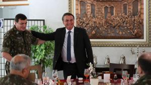 Em pé, sorridente e com a mão no ombro do comandante do Exército, Paulo Sérgio Nogueira, Jair Bolsonaro fala com oficiais durante visita à instalação militar