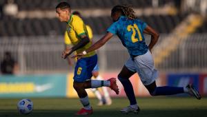 Marcado por Vasco Lopes, camisa 21 de Cabo Verde, que aparece de costas, Guilherme Arana parte com a bola dominada durante jogo da seleção olímpica