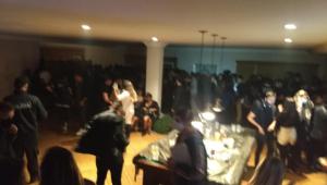 Imagem desfocada mostra dezenas de pessoas em uma ampla sala de uma casa de luxo em Campos do Jordão; algumas delas escondem o rosto devido à presença de policiais