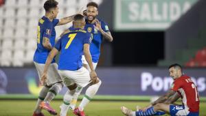 Após marcar contra o Paraguai, Neymar abre sorriso e vai de encontro a Firmino e Gabriel Jesus, que aparecem de costa; no fundo, jogador paraguaio está sentado no gramado, desolado