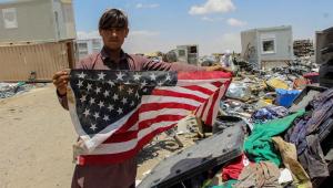 Homem afegão mostra bandeira dos Estados Unidos em centro de venda de objetos deixados pelas tropas norte-americanas antes da sua saída