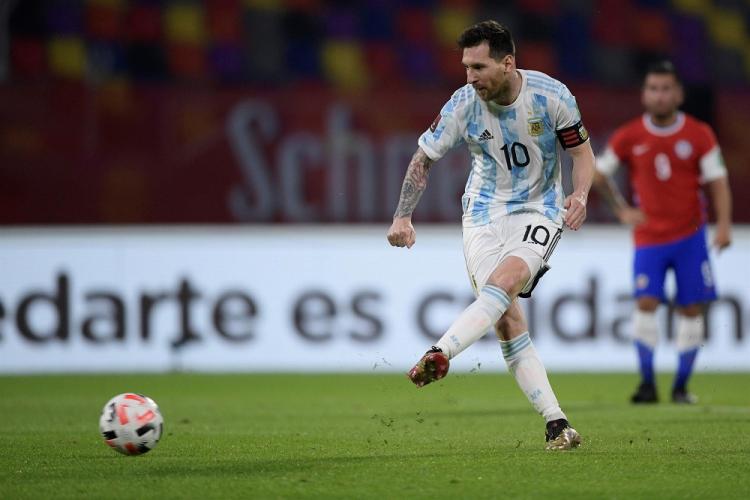 Lionel Messi chuta a bola com a perna esquerda durante jogo contra o Chile; jogador rival aparece desfocado