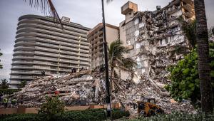 Vários destroços e uma parte desmoronada de um edifício grande em Miami. Ao lado, construções grandes ainda de pé.