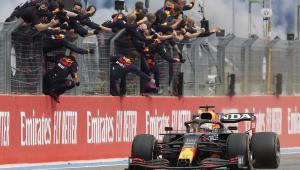 Integrantes da equipe Red Bull comemoram no alambrado enquanto Max Verstappen anda com seu carro na pista após confirmar a vitória no GP da França