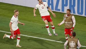 Perto da linha de fundo, o atacante Lewandowski salta em direção aos reservas da Polônia para comemorar seu gol