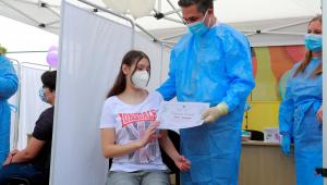 Menina recebe certificado de vacinação contra a Covid-19 em posto na Romênia
