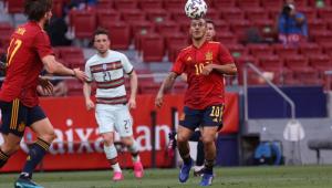 Vestido com a camisa vermelha e o shorts azul da seleção espanhola, Thiago Alcântara amortece a bola na cabeça durante jogo contra Portugal; um companheiro está perto dele e um rival o observa de trás