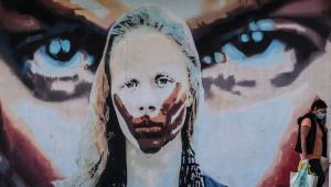 Mulher caminha diante de um grafite representando uma mulher sendo calada na Avenida dos Bandeirantes