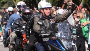 Jair Bolsonaro em moto acenando a apoiadores