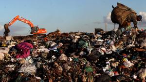 Pessoa catando lixo em lixão e máquina laranja no fundo