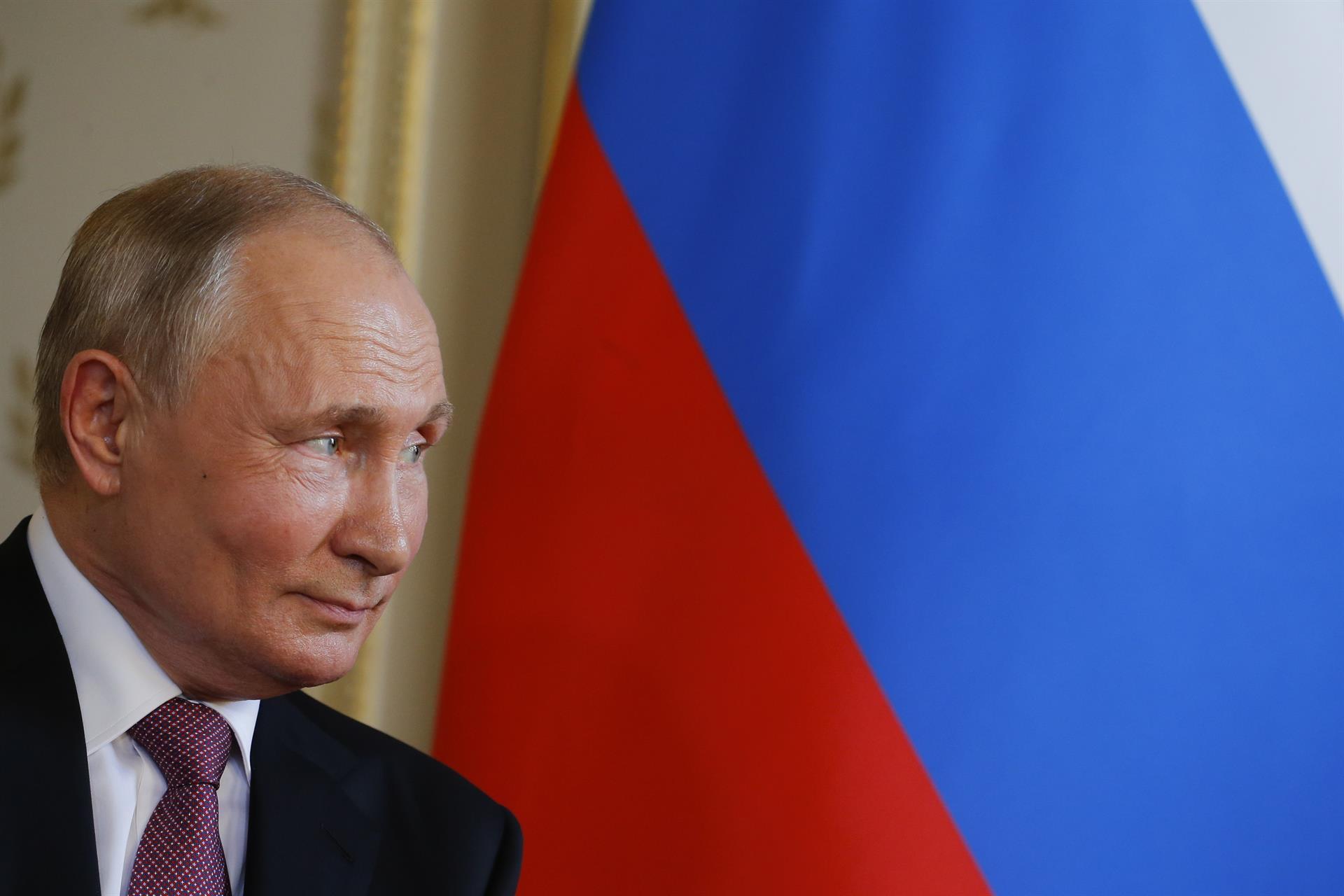 Vladimir Putin de perfil em frente a bandeira da Rússia