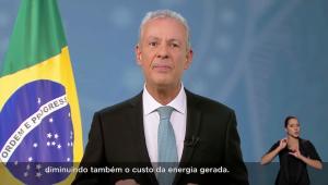 Ministro Bento Albuquerque, homem de terno preto, camisa branca e gravata azul, falando na televisão. Ao lado, uma bandeira do Brasil sem estar hasteada