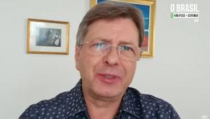 Com uma camisa azul escura de mangas curtas, estampada com bolinhas azuis claras, óculos, e cabelo loiro penteado para o lado, o deputado Bibo Nunes grava depoimento em um cômodo com dois quadros atrás dele