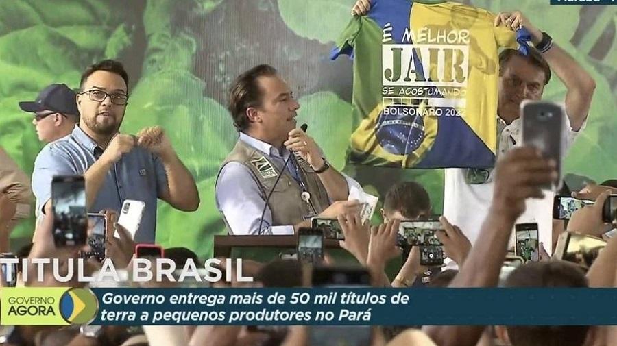 """Transmissão da TV Brasil mostra Bolsonaro segurando uma camiseta com a mensagem """"É melhor Jair se acostumando. Bolsonaro 2022"""""""