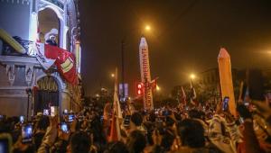 Da sacada da sede do partido Peru Livre, Pedro Castillo fala para uma multidão do lado de fora, onde se vê, em meio às pessoas, dois lápis infláveis que simbolizam a profissão do candidato de esquerda (professor)
