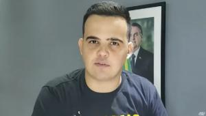 De camiseta cinza escura, em um cômodo com paredes cinzas e um quadro de Jair Bolsonaro pendurado, o deputado Cano Junio Amaral (homem branco, cabelo preto curto e ondulado, 33 anos) grava depoimento para a Jovem Pan