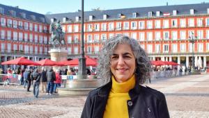 Mulher olhando para foto com uma blusa de lã amarela e um casaco preto. Ela tem cabelos grisalhos e está em um cenário que é a Plaza Mayor, com uma estátua e prédios baixos em volta
