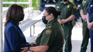 Kamala Harris apertando mão de guarda na fronteira