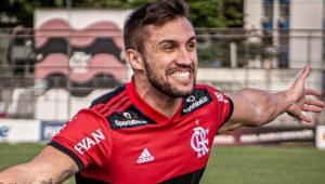 Arthur Picoli correndo de braços abertos em um campo de futebol