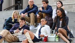 Elendo do reboot de Gossip Girl caracterizado e sentado em uma escada