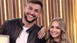 Arthur sorrindo ao lado de Carla Diaz, que está com a mão em seu ombro