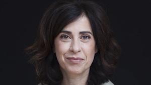 Fernanda Torres em um local com fundo preto dando um leve sorriso