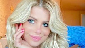 Karina Bacchi com a mão no rosto e sorrindo
