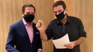 João Doria, de terno azul marinho, camisa azul claro e máscara, e Eduardo Paes, de camisa grená com manga dobrada, óculos escuros preso na gola e também de máscara, gravam vídeo juntos para celebrar acordo por vacinas