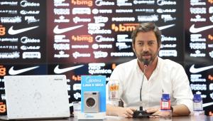 De camisa branca, sentado na sala de imprensa do centro de treinamento do Corinthians, à frente de um banner de patrocinadores e com alguns produtos espalhados pela mesa, Duílio Monteiro Alves dá entrevista
