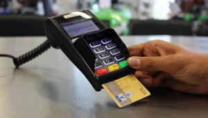 Sobre uma mesa, uma mão segura uma maquininha com o cartão dentro