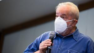 O ex-presidente Lula discursando com máscara e com microfone na mão
