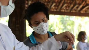 Enfermeira mostrando frasco de vacina contra Covid-19