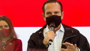 De jaqueta preta, camisa xadrez e máscara preta, JoãoDoria fala segurando o microfone na mão direita