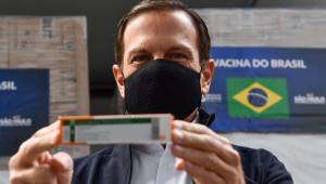 O governador de São Paulo, João Doria, mostra uma caixa da Coronavac