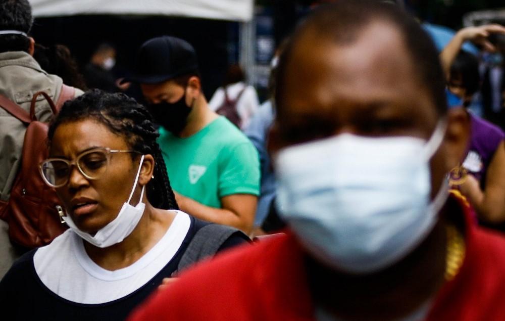 Na Avenida Paulista, mulher negra usa máscara no queixo; imagem mostra outras pessoas ao redor, todas com máscara