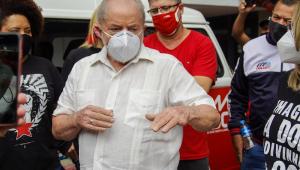 De máscara e camisa bege, Lula discursa rodeado por militantes do PT