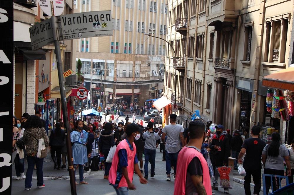 Dezenas de pessoas, algumas sem máscaras, se movimentam na ladeira Porto Geral, na região da 25 de Março, em São Paulo