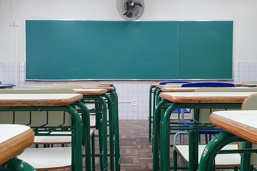 Vista de trás de uma sala de aula, com a lousa de frente para quem olha a imagem e um vão entre as carteiras, alinhadas lado a lado