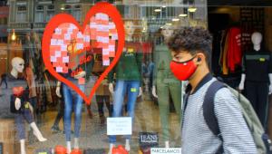 Usando máscara, homem passa na frente de uma loja com decoração para o dia dos Namorados
